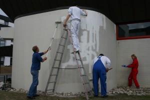 Mitglieder des Fördervereins streichen die Westfassade des Hallenbads